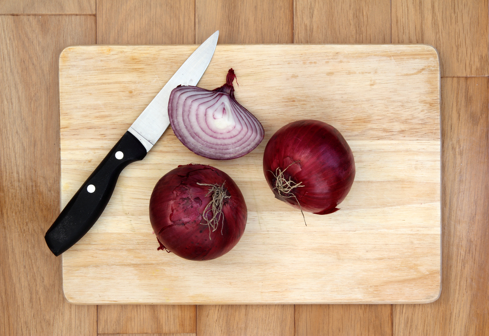Red onions and knife on a wooden chopping board