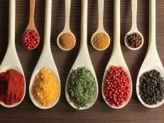 Various spices on wooden spoons