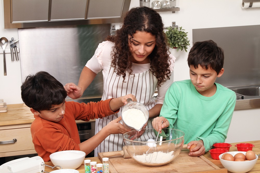 Woman and two children baking