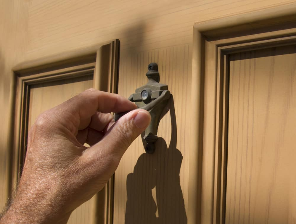 Man's hand using door knocker