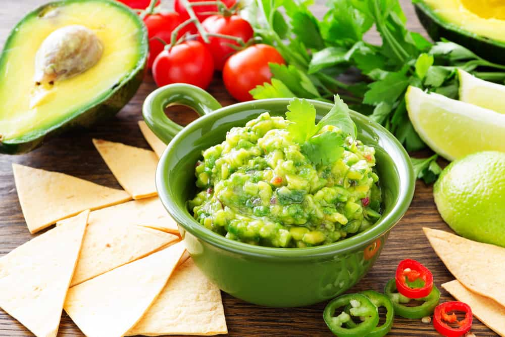 Green ceramic bowl filled with guacamole